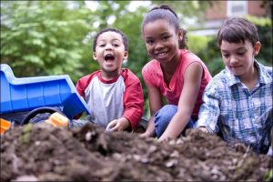 Close up of three children playing on the ground, with a pile of dirt in front of them and a blue toy truck next to them