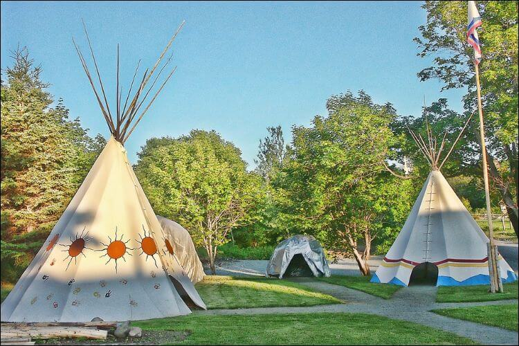 Several colorful children teepees in a backyard with green lawn