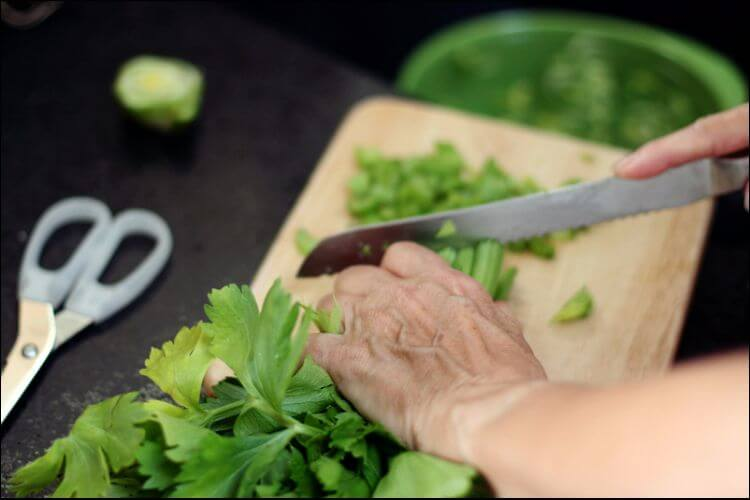 White man hands chopping celery on a wooden surface