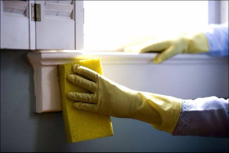 Focus on a person with yellow gloves on cleaning with a yellow sponge a white piece of wood from a furniture or window