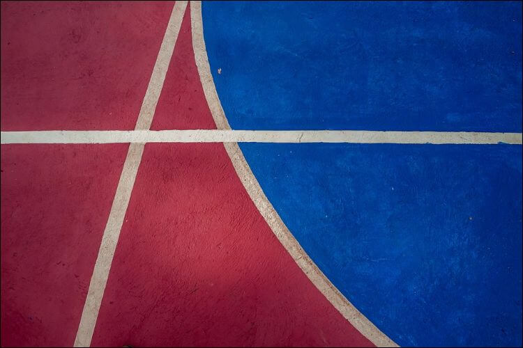 Close up of a colored flooring for a basketball court, in red and blue, with intersecting white lines