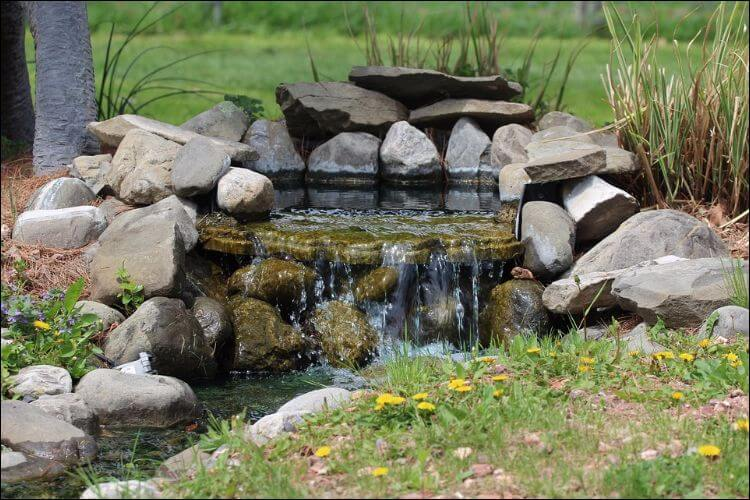 Waterfall design for the backyard with stones and grass