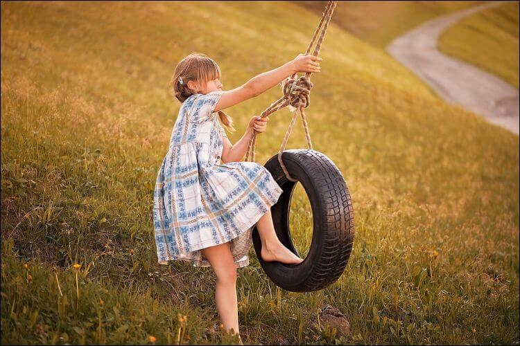 Blonde girl in a white and blue dress swinging on a tire swing against a yellow grass background