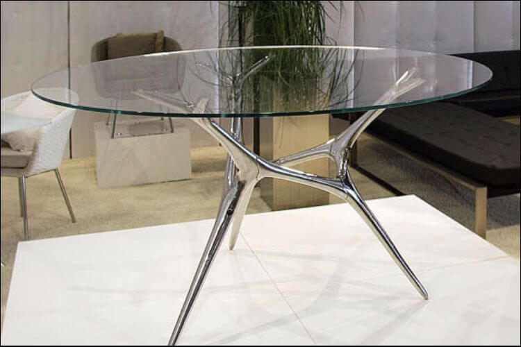 Close up of a glass table placed on a white pedestal, with armchairs in the background