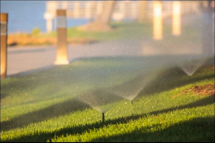 Close up of an irrigation system with three sprinklers turned on