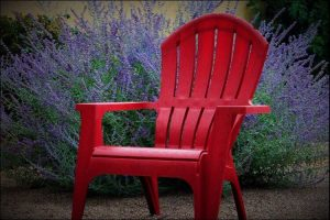 Focus on a red lounge plastic chair set against a background of lavender plants
