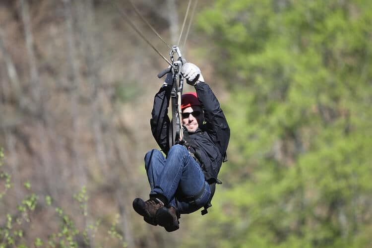 Focus on a man dressed for winter, ziplining
