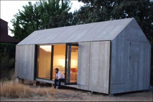 Minimalist studio shed, with simple beige walls, placed on the ground in front of trees