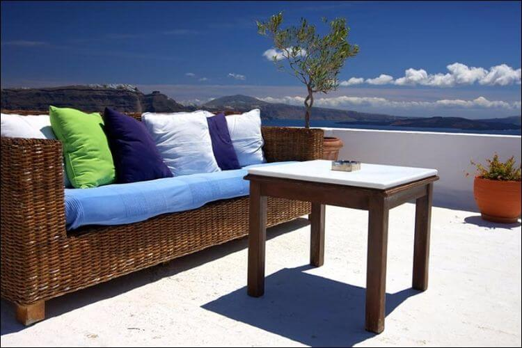Outdoor set with a couch and a table, with colorful cushions and a small mattress on the couch