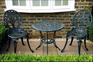 Outdoor wrought iron furniture set in a black color, set in front of a white window, on a gray paving