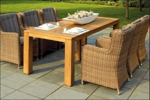 Outdoor set with six rattan chairs and a wooden table in the middle, with a huge bowl of food and two plates on it