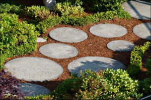 Small space with red soil and grey round pavers placed randomly on it, surrounded by green bushes