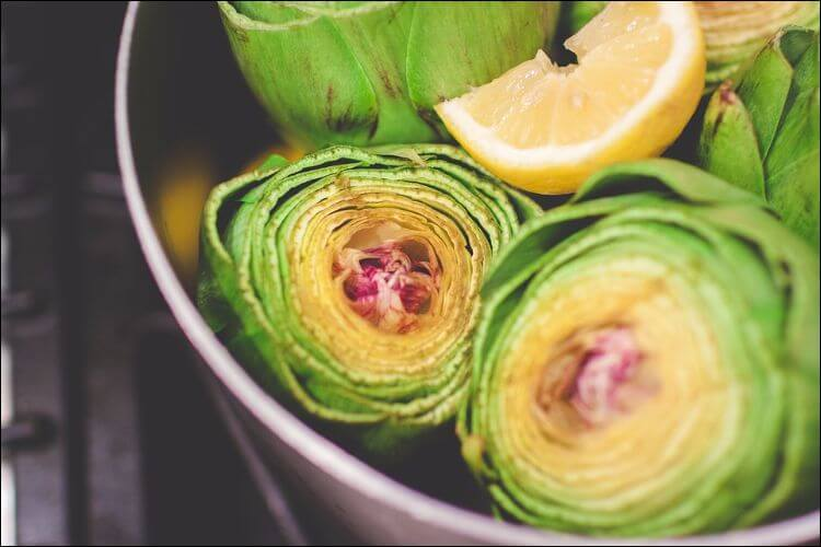 Close up of a halved artichoke in green, yellow, and purple colors, placed in a bowl with other artichokes and a lemon quarter on them