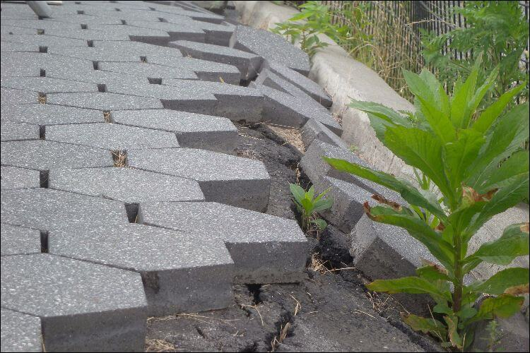 Close up of some sliding pavers heading towards a patch of grass