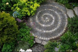 A round focal point with a spiral pattern made of gray and white pavers, surrounded by green bushes and flowers