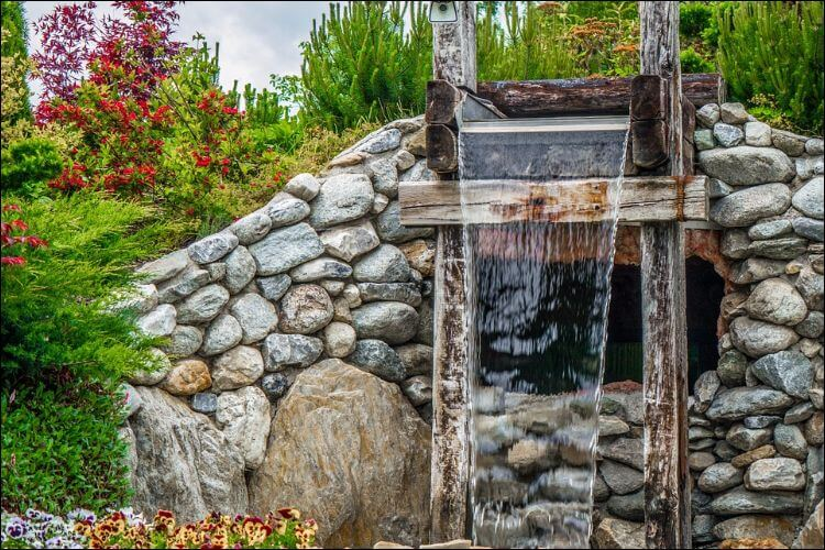 Stone waterfall placed in a trees landscape in a backyard
