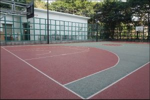 View of a basketball court with a colored surface in red and green on it, with white lines, surrounded by a green fence, with a building and green trees in the background