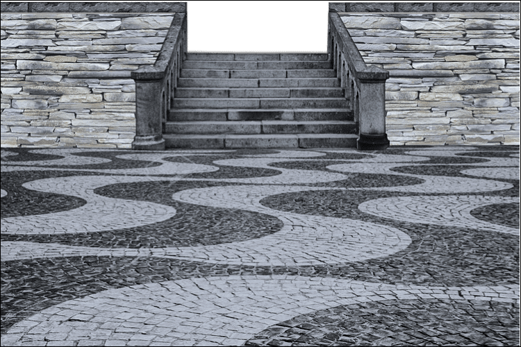 Close up of a ground with pavers set in a winding pattern, alternating between white and gray, with stone walls and stairs in the background