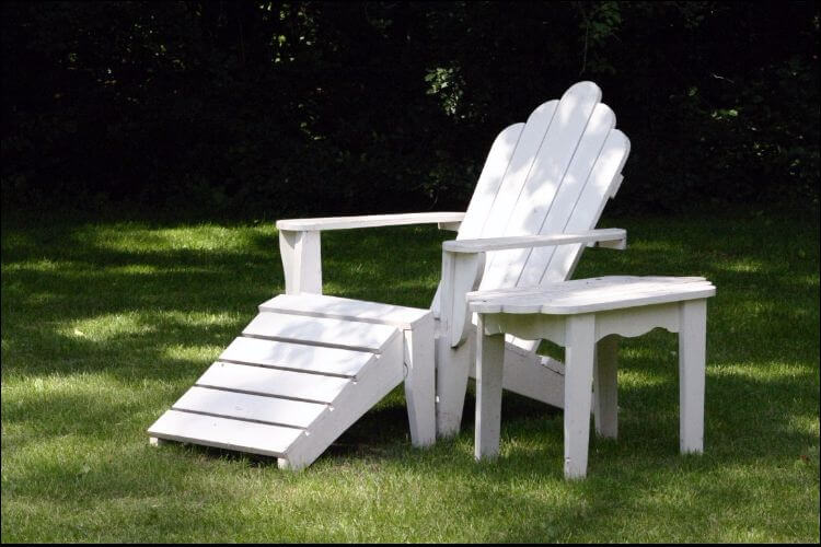 White wooden chair sitting on the lawn next to a small white wooden table - Complete Guide On How To Waterproof Wood Furniture For Outdoors