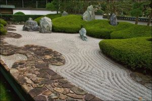 Winding pathway made of colored pavers, placed next to a larger gravel pathway, surrounded by green thick bushes with big boulders placed here and there