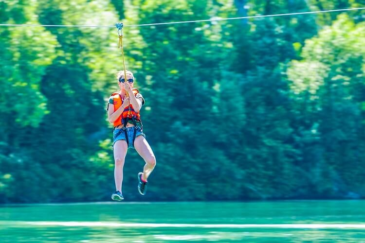 Focus on a woman ziplining over a body of water