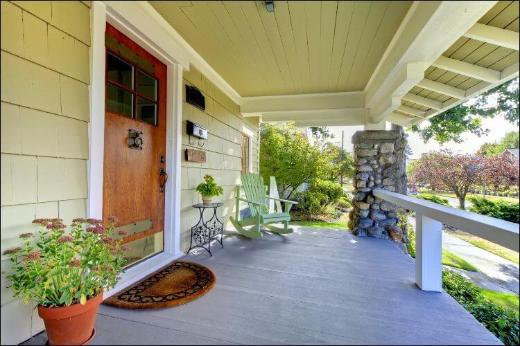landscaping ideas for front porch wide porch with flower pots, chairs, and trees outside of it