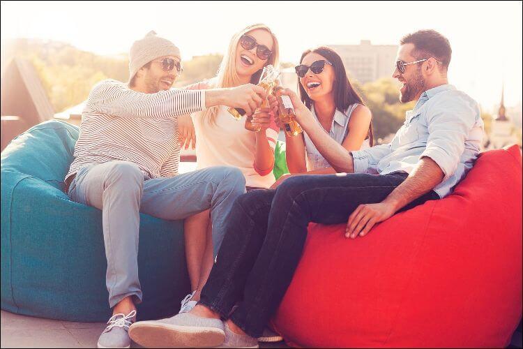 DIY backyard movie screen four friends drinking
