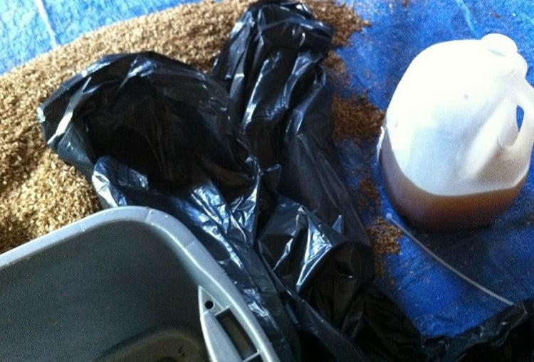 Preparing bokashi mixture in a bin