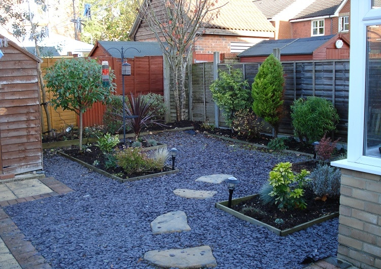 Garden with no grass, with tiles and gravel on the ground