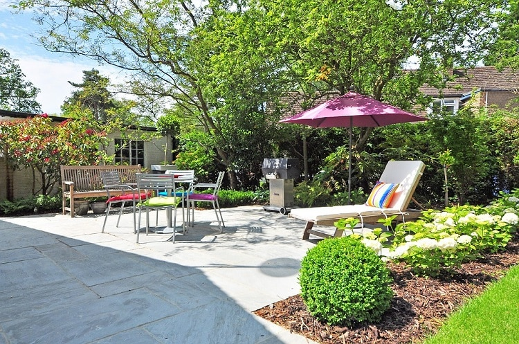 Grassless backyard with chairs, a table, an umbrella, and a chaise-longue