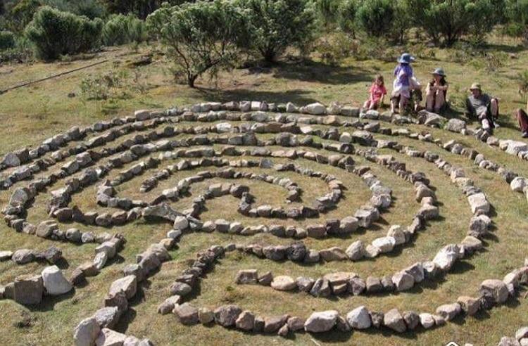 Kids sitting next to a stone labyrinth