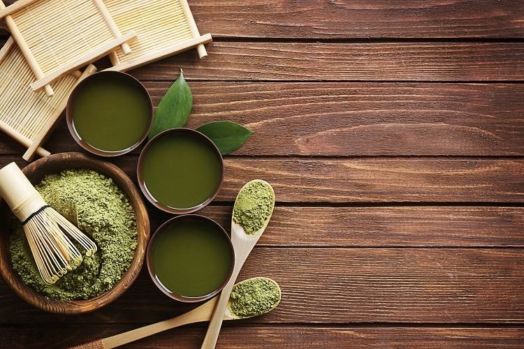 Matcha powder and three cups of green tea
