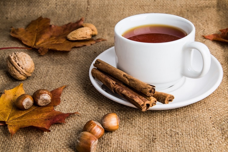 Tea in a cup next to several autumn decorations