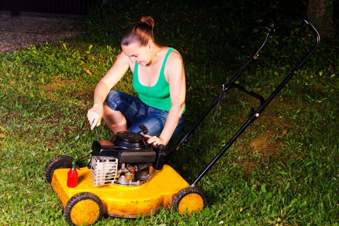 woman repairing lawnmower