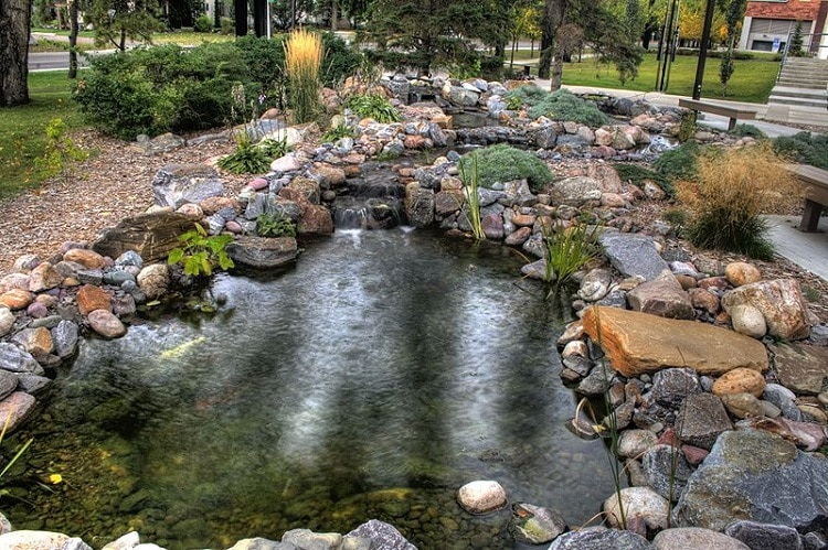 DIY pool edged by plenty of river stones