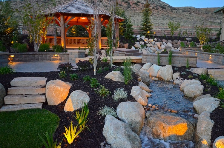 Hardscape and softscape garden with a pond, stones, and vegetation