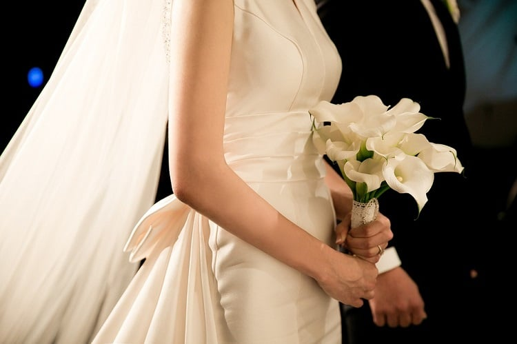 Bride holding a lily bouquet