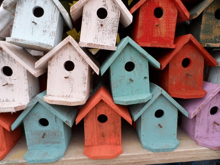 Several birdhouses painted in red, blue, and white