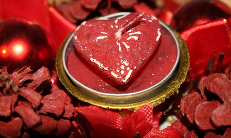 Heart candle in a metallic cup among red decorations