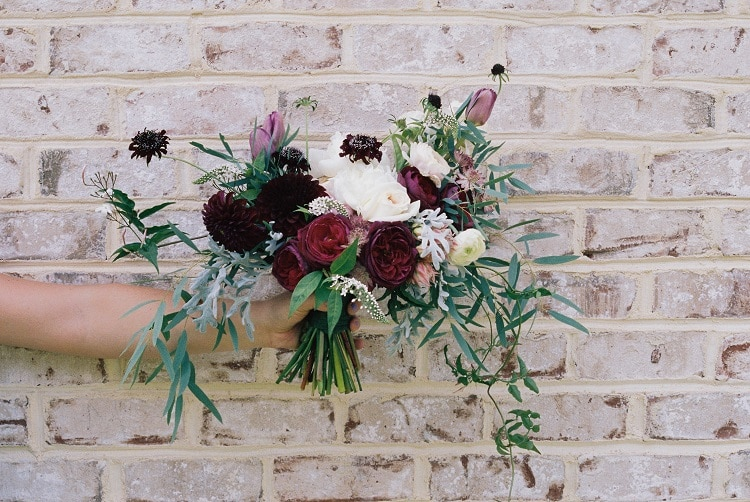 Holding a flower bouquet in front of a brick wall, wedding flower wall