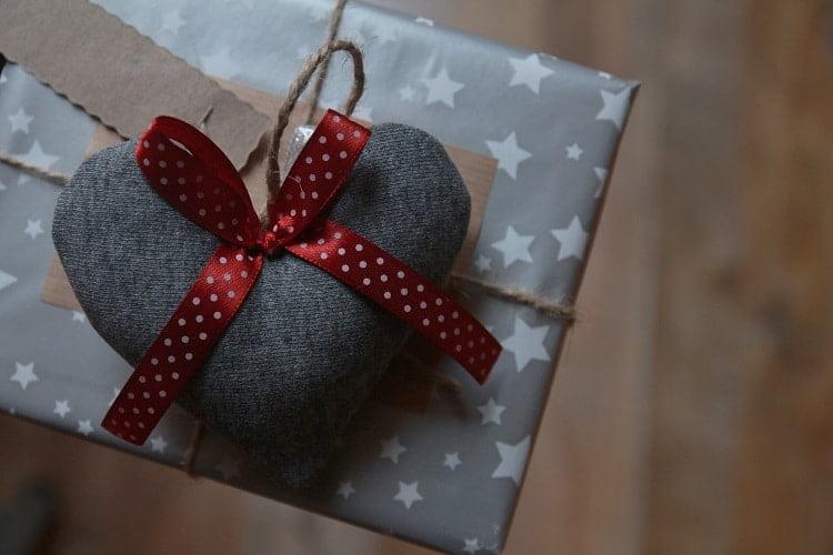 Grey heart needle pillow on a present