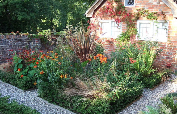 Garden full of native plants next to a brick house