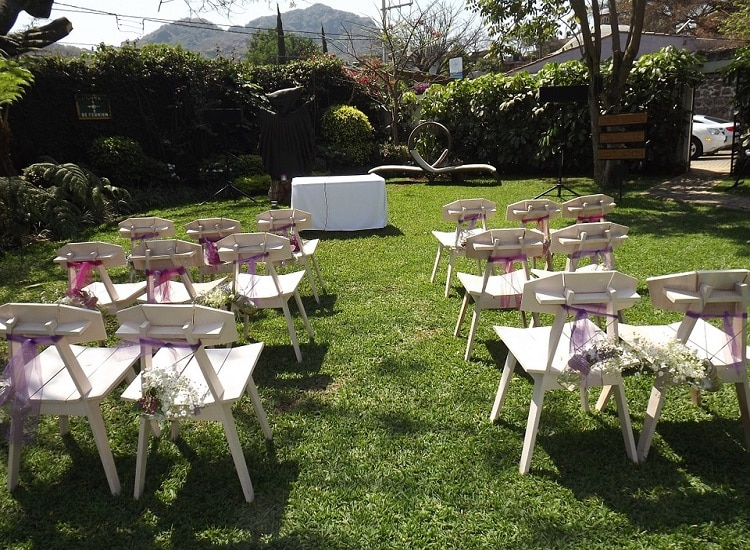 row of white chair placed for a wedding in a backyard