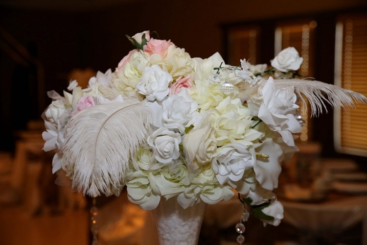 White wedding flowers placed in an arrangement with feathers