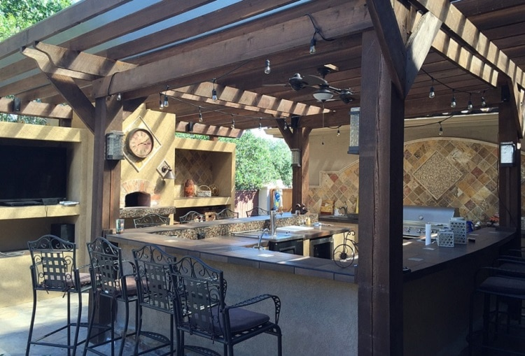 Outdoor kitchen on a patio under a nice wooden cover