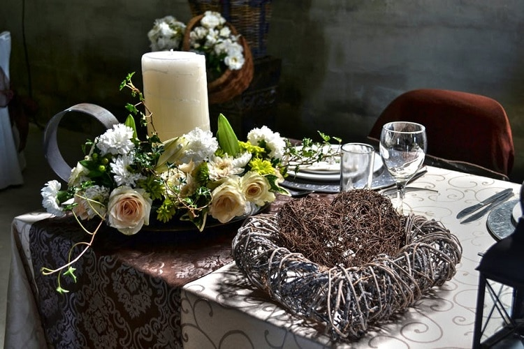 Flower arrangement surrounding a white candle on a table next to a heart made of twigs