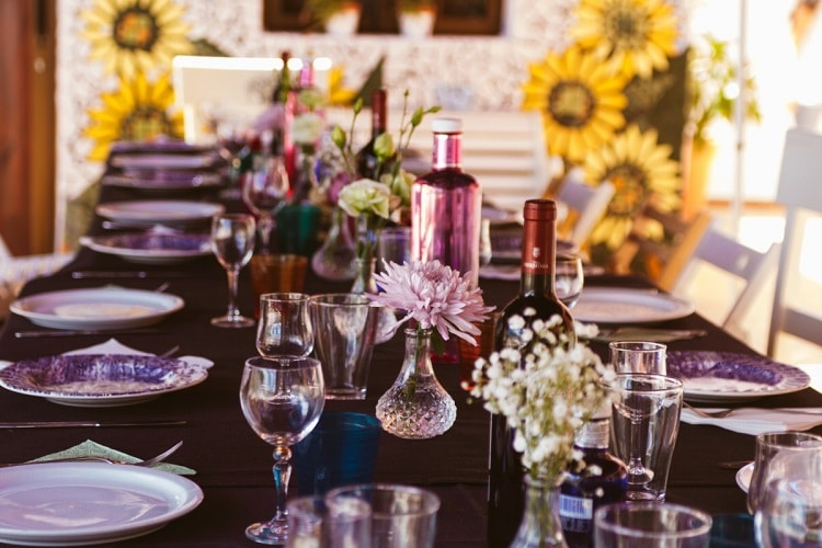 Wedding table with crystal glasses and meadow flowers in vases