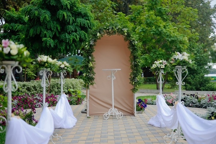green arch against green outdoor backdrop with white decorated pillars making up an aisle