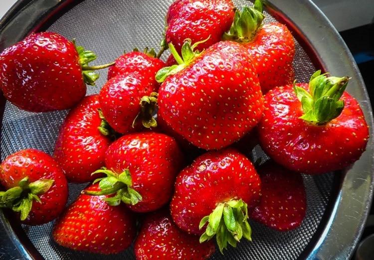 Strawberries sitting in a strainer